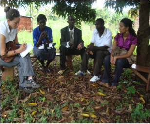 Agnes Akello meets with village officials while other students observe